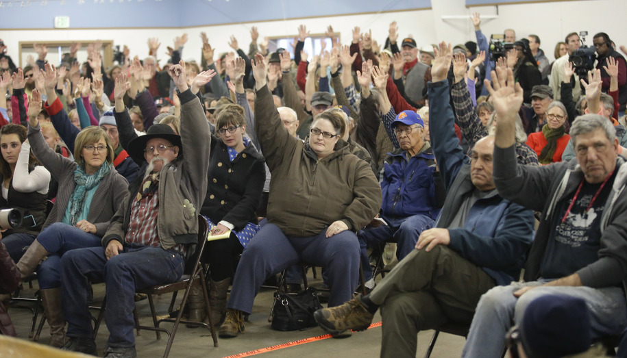 Residents raise their hands as Harney County Sheriff David Ward addresses their concerns at a community meeting at the Harney County fairgrounds Wednesday, Jan. 6, 2016, in Burns, Ore. With the takeover entering its fourth day Wednesday, authorities had n