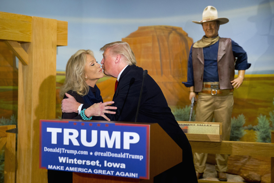 A wax statue of John Wayne watches as Republican presidential candidate Donald Trump kisses John Wayne's daughter, Aissa, during a news conference at the John Wayne Museum, Tuesday, Jan. 19, 2016, in Winterset, Iowa. (AP Photo/Jae C. Hong)