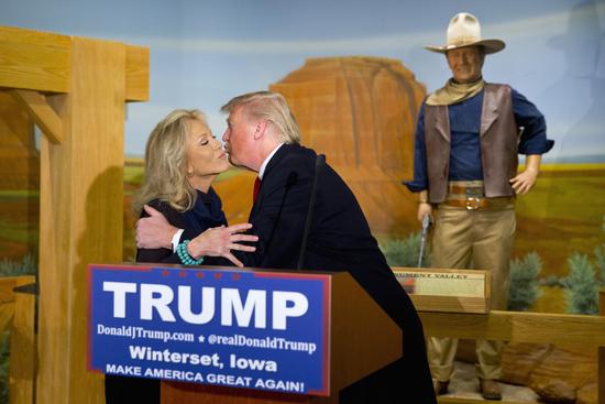 A wax statue of John Wayne watches as Republican presidential candidate Donald Trump kisses John Wayne's daughter, Aissa, during a news conference at the John Wayne Museum, Tuesday, Jan. 19, 2016, in Winterset, Iowa. (AP Photo/Jae C. Hong)