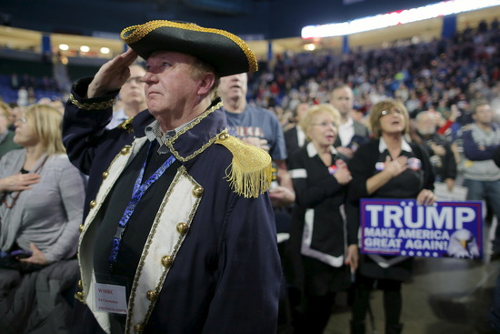 Edward Champigny salutes during the playing of the U.S. national anthem at a campaign rally with U.S. Republican presidential candidate Donald Trump in Lowell, Massachusetts January 4, 2016. REUTERS/Brian Snyder - RTX211J6