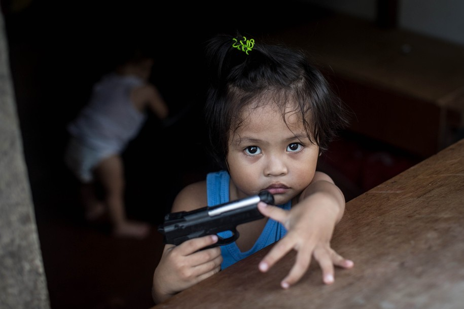 TACLOBAN, LEYTE, PHILIPPINES - AUGUST 13: A young girl plays with a toy gun in the coastal area renamed by residents ' Yolanda Village' on August 13, 2014 in Tacloban, Leyte, Philippines. Tacloban residents continue to focus on rebuilding their lives nine