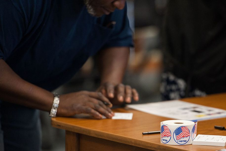 Voting stickers are seen as a man is checked in to receive his ballot during Missouri primary voting at the Griffith Elementary School on March 15, 2016 in Ferguson, Missouri..Voters began going to the polls Tuesday in five make-or-break presidential nominating contests, with Republican Donald Trump and Democrat Hillary Clinton seeking to tighten their grip as their party's front runners. / AFP / Michael B. Thomas        (Photo credit should read MICHAEL B. THOMAS/AFP/Getty Images)