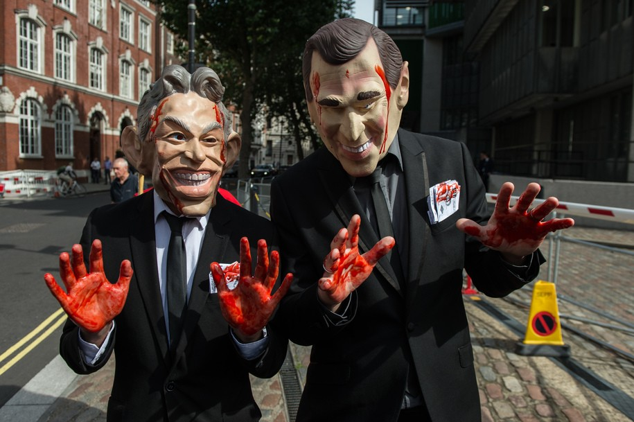 LONDON, ENGLAND - JULY 06:  Demonstrators dressed as former British Prime Minister Tony Blair and former US President George Bush Jr arrive with painted red hands and in hand cuffs outside the Queen Elizabeth II conference centre on July 6, 2016 in London, England. The Iraq Inquiry Report into the UK government's involvement in the 2003 Iraq War under the leadership of Tony Blair is published today.  The inquiry, which concluded in February 2011, was announced by then Prime Minister Gordon Brown in 2009 and is published more than seven years later. (Photo by Chris J Ratcliffe/Getty Images)
