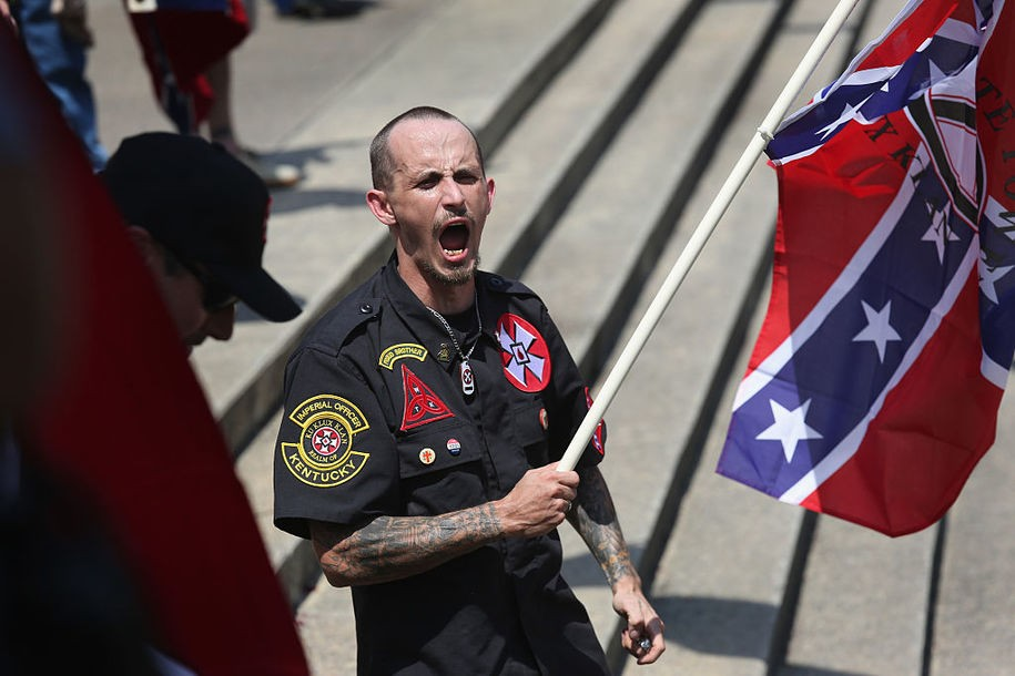 COLUMBIA, SC - JULY 18:  A Ku Klux Klan member shouts racial slurs to African Americans at a Klan demonstration at the state house building on July 18, 2015 in Columbia, South Carolina. The KKK protested the removal of the Confederate flag from the state house grounds, as law enforcement tried to prevent violence between the opposing groups.  (Photo by John Moore/Getty Images)