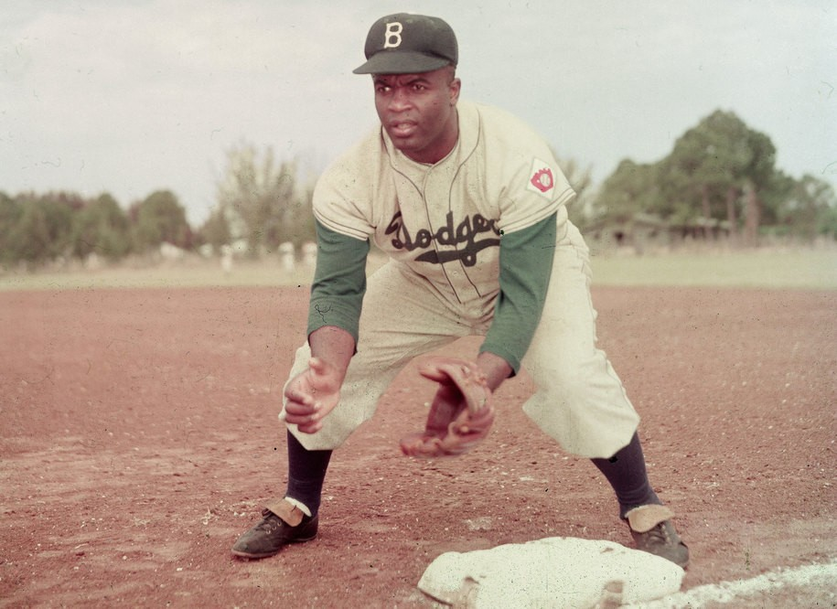 American professional baseball player Jackie Robinson [1919 - 1972) of the Brooklyn Dodgers, dressed in a road uniform, crouches by the base and prepares to catch a ball, 1951. Throughout the course of his baseball career Robinson played several positions on the infield as well as serving as outfielder. (Photo by Keystone/Getty Images)