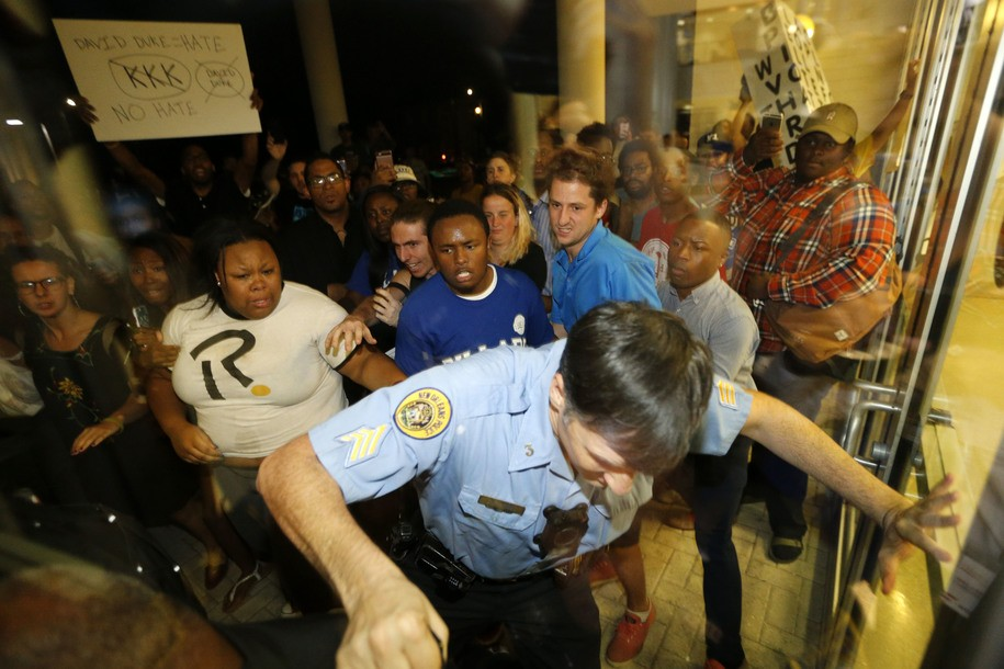A police officer pushes his way outside to keep protesters at bay, before a debate for Louisiana candidates for the U.S. Senate, at Dillard University in New Orleans, Wednesday, Nov. 2, 2016. They were protesting the presence of former Ku Klux Klan leader and current U.S. Senate candidate David Duke, who was participating in the debate at the historically black college. (AP Photo/Gerald Herbert)