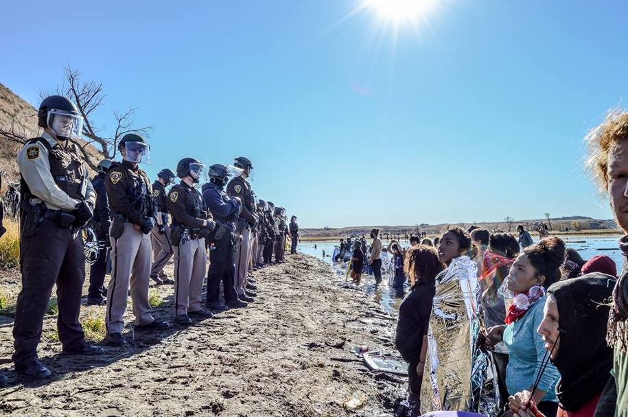 Water Protectors holding ceremony at the Cannon Ball River are met with a line of Riot Police.