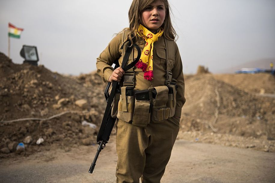 TOPSHOT - A Kurdish girl wears her relative's assault rifle and ammunition belt as she waits at the  Iraqi Kurdish Shaqouli checkpoint, some 35 kilometres east of Mosul, on November 10, 2016. .Since the start of the Mosul offensive the Kurds have moved their border some 10 kms closer to Iraq's second city, marking it out with a line in the sand. / AFP / Odd ANDERSEN        (Photo credit should read ODD ANDERSEN/AFP/Getty Images)