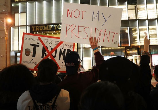 NEW YORK, NY - NOVEMBER 10:  Dozens of anti-Donald Trump protesters stand along 5th Avenue in front of Trump Tower as New Yorkers react for a second night to the election of Trump as president of the United States on November 10, 2016 in New York City. Trump defeated Democrat Hillary Clinton to become the 45th president.  (Photo by Spencer Platt/Getty Images)