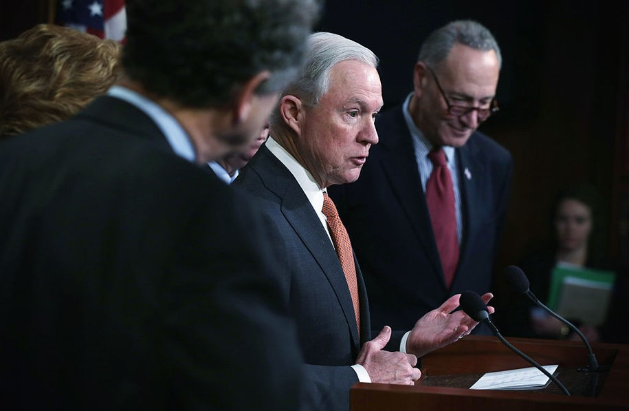 WASHINGTON, DC - FEBRUARY 10:  U.S. Sen. Jeff Sessions (R-AL) (L) speaks as Sen. Charles Schumer (D-NY) (R) listens during a news conference on currency and trade February 10, 2015 on Capitol Hill in Washington, DC. A group of bipartisan senators will introduce the Currency Exchange Rate Oversight Reform Act of 2015 to combat currency manipulation and create jobs as the same time.  (Photo by Alex Wong/Getty Images)