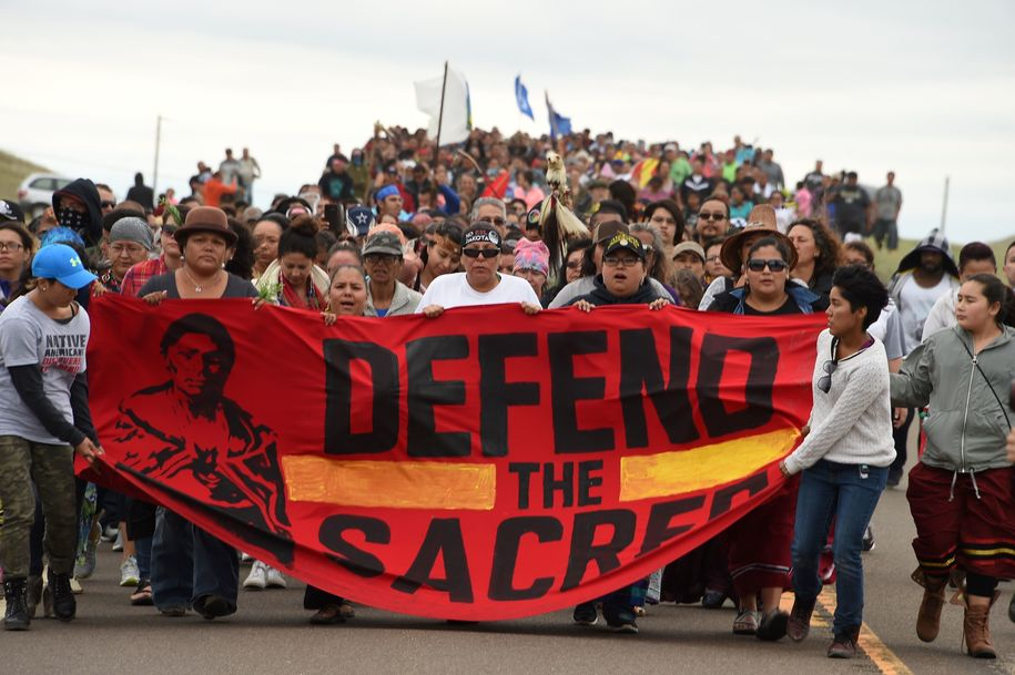 Native Americans march to the site of a sacred burial ground that was disturbed by bulldozers building the Dakota Access Pipeline (DAPL), near the encampment where hundreds of people have gathered to join the Standing Rock Sioux Tribe's protest of the oil pipeline slated to cross the nearby Missouri River, September 4, 2016 near Cannon Ball, North Dakota.  .Protestors were attacked by dogs and sprayed with an eye and respiratory irritant yesterday when they arrived at the site to protest after learning of the bulldozing work. / AFP / ROBYN BECK        (Photo credit should read ROBYN BECK/AFP/Getty Images)