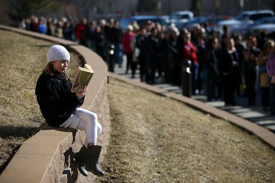 """COUNCIL BLUFFS, IA - JANUARY 31:  A young girl reads a book as people wait in line to enter a """"get out to caucus"""" event for democratic presidential candidate former Secretary of State Hillary Clinton  at Abraham Lincoln High School on January 31, 2016 in Council Bluffs, Iowa.  With one day to go before the Iowa caucuses, Hillary Clinton continues to campaign throughout Iowa.  (Photo by Justin Sullivan/Getty Images)"""