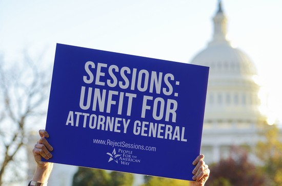 WASHINGTON, DC - NOVEMBER 18:  Drew Courtney, Director of Communications for People for the American Way holds a sign to call on senate to reject Jeff Sessions as Attorney General on November 18, 2016 in Washington, DC.  (Photo by Leigh Vogel/Getty Images for People For The American Way)