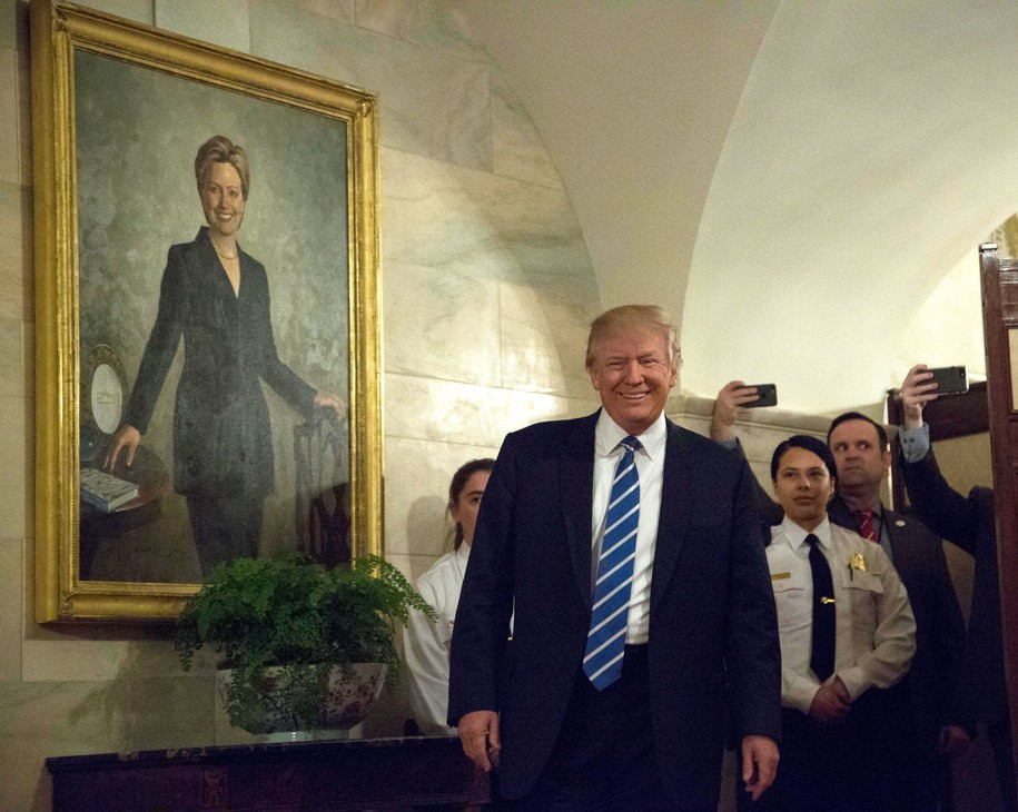 US President Donald Trump Greets Visitors In The White House WASHINGTON, DC - MARCH 07: U.S. President Donald Trump walks in a corridor of the White House to greet visitors, while a portrait of Hillary Clinton hangs on the wall, March 7, 2017 in Washington, DC . (Photo by Aude Guerrucci-Pool/Getty Images)