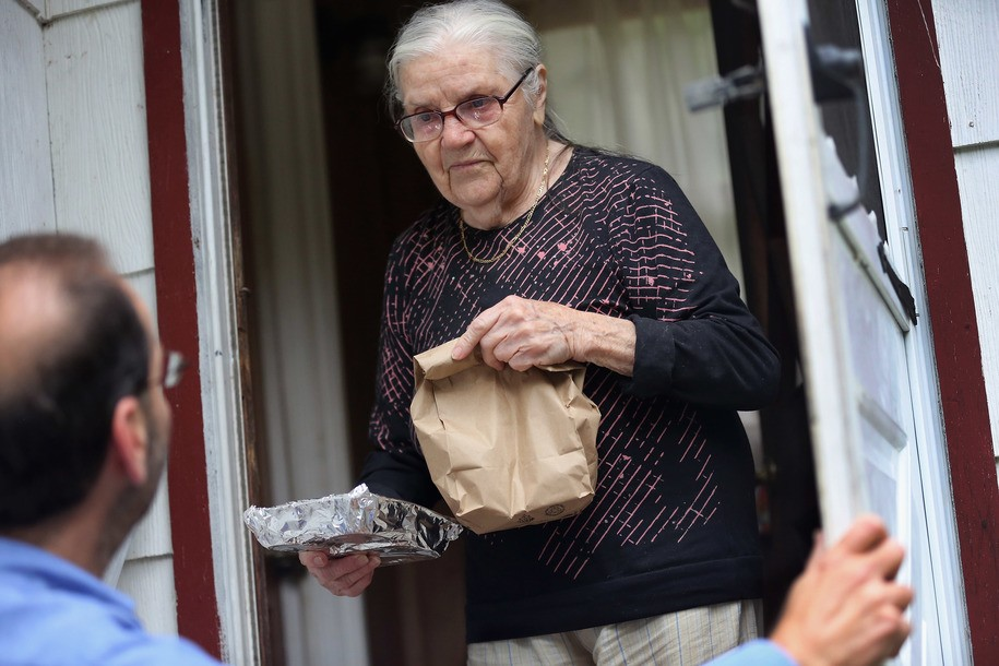 "GLEN SPEY, NY - SEPTEMBER 21:  Tamara Lycholaj, 89, receives a hot meal from nutrition worker Al Patalona from the Sullivan County Office for the Aging as he makes ""Meals on Wheels"" deliveries to elderly rural residents on September 21, 2012 in Glen Spey, New York. He and colleagues deliver hot meals to hundreds of homebound seniors with limited mobility in the rural upstate New York county. The nutrition program is funded by federal, state and county grants.  (Photo by John Moore/Getty Images)"