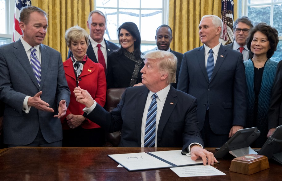 WASHINGTON, DC - MARCH 13: President Donald Trump hands his pen to Director of the Office of Management and Budget (OMB) Mick Mulvaney (front-L), after signing an executive order entitled, 'Comprehensive Plan for Reorganizing the Executive Branch', beside members of his cabinet in the Oval Office of the White House on March 17, 2017 in Washington, DC. Also pictured are Administrator of the Small Business Administration Linda McMahon (2-L), Secretary of the Interior Ryan Zinke (3-L), US Ambassador to the UN Nikki Haley (4-L), Secretary of Housing and Urban Developement (HUD) Ben Carson (Back C), Vice President Mike Pence (3-R), Secretary of Energy Rick Perry (2-R) and Secretary of Transportation Elaine Chao (R).  (Photo by Michael Reynolds-Pool/Getty Images)