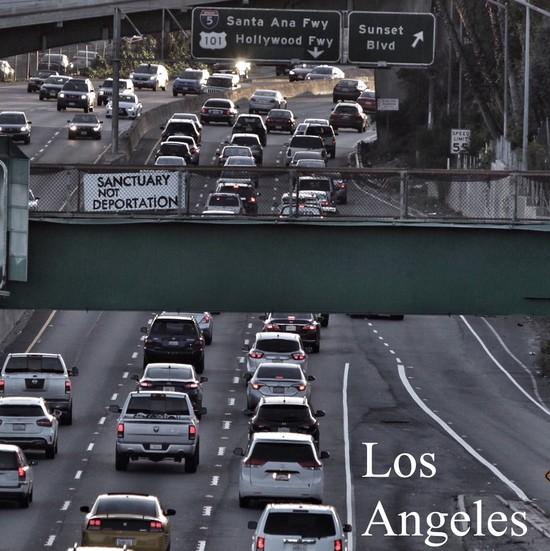 Sanctuary Not Deportation sign over LA Freeway.