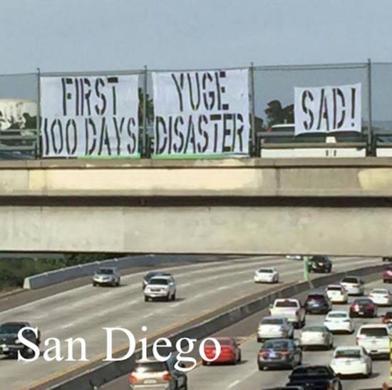First 100 Days Yuge Disaster Sad! sign over I-5 in San Diego.