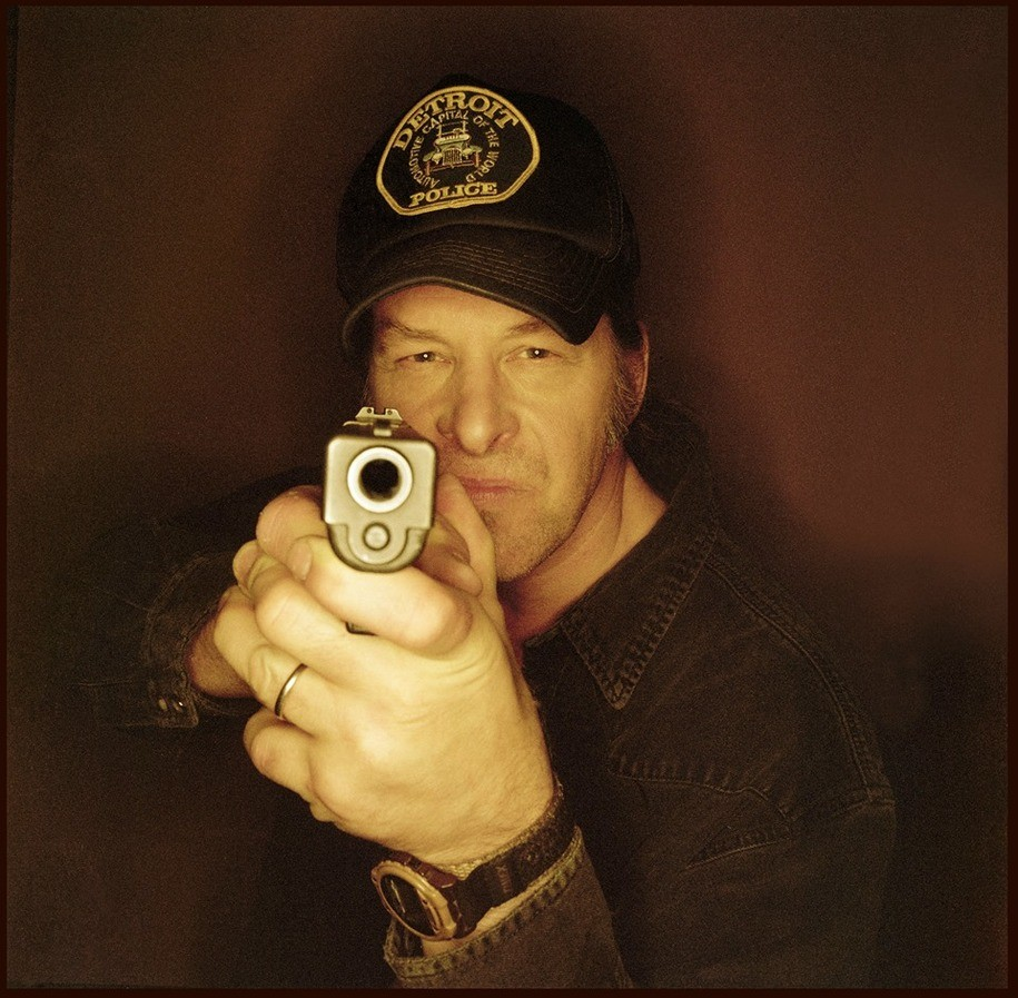 Ted Nugent pointing a gun at a camera