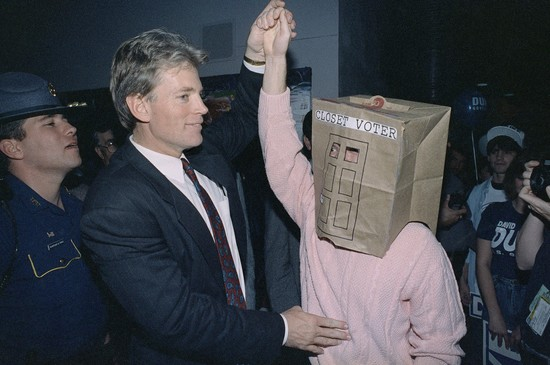 Louisiana Republican gubernatorial candidate David Duke meets with an unidentified supporter during a rally in Benton, Louisiana, Nov. 15, 1991. The supporter wears a paper bag over his head identifying himself as a closet voter. (AP photo/Tannen Maury)