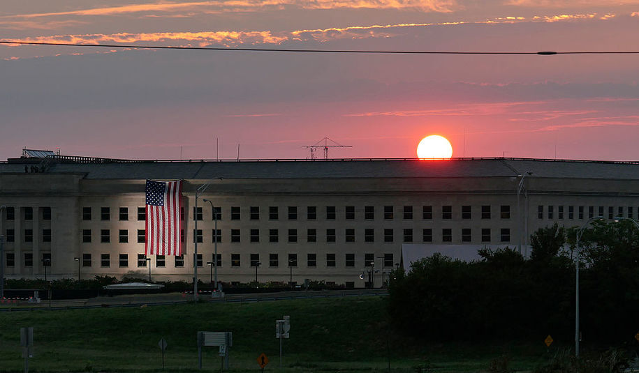 ARLINGTON, VA - SEPTEMBER 11: In this U.S. Navy handout, sunrise at the Pentagon prior to a ceremony to commemorate the 15th anniversary of the Sept. 11, 2001 terror attacks. The American flag is draped over the site of impact at the Pentagon.  In 2008, the National 9/11 Pentagon Memorial opened  adjacent to the site, located on Boundary Channel Drive in Arlington, Va., and commemorates the 184 lives lost at the Pentagon and onboard American Airlines Flight 77 during the terrorist attacks. (Photo by Damon J. Moritz/Released via Getty Images