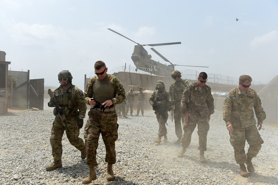 "TO GO WITH AFGHANISTAN-US-ARMY-CONFLICT-FOCUS BY GUILLAUME DECAMME.In this photograph taken on August 13, 2015, US army soldiers walk as a NATO helicopter flies overhead at coalition force Forward Operating Base (FOB) Connelly in the Khogyani district in the eastern province of Nangarhar. From his watchtower in insurgency-wracked eastern Afghanistan, US army Specialist Josh Whitten doesn't have much to say about his Afghan colleagues. ""They don't come up here anymore, because they used to mess around with our stuff. ""Welcome to Forward Operating Base Connelly, where US troops are providing training and tactical advice to the 201st Afghan army corps as they take on the Taliban on the battlefield. AFP PHOTO / Wakil Kohsar (Photo credit should read WAKIL KOHSAR/AFP/Getty Images)"