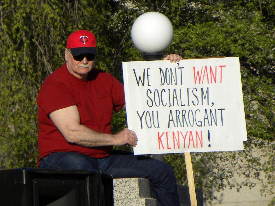 """Man holding poster that reads: """"We don't want socialism, you arrogant Kenyan!"""" during April 15, 2010 tea party protest in St Paul, MN"""