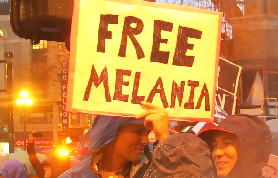 "Protesters in the rain with giant red sign saying ""FREE MELANIA"" in large, black handwritten text."