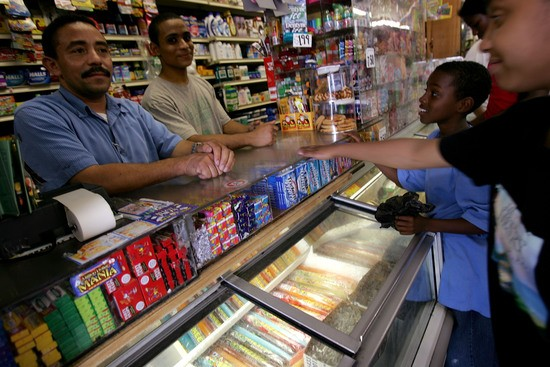 NEW YORK - JUNE 18: Jesus Martinez (left) works in a Bodega grocery store near where Bolivar Cruz was killed while working in Bodega last week on June 18, 2007 in Queens, New York City.  Sixteen stores in the Bodega region have been robbed since March.  While crime has decreased across New York City, running a bodega is still a risky job because many customers are poor and stores are often located in high-crime areas.  (Photo by Spencer Platt/Getty Images)