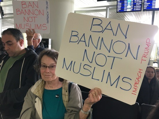 Signs seen at the Muslim Ban protest at SFO International Terminal on January 29, 2016. Text reads: BAN BANNON NOT MUSLIMS, IMPEACH TRUMP