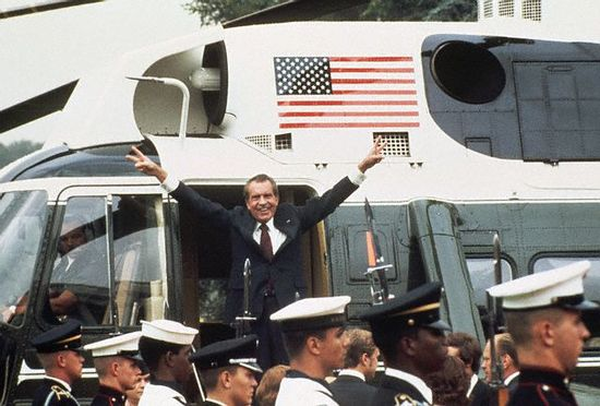 Richard M. Nixon, following his resignation from the office of President of the United States on August 9, 1974, waves the victory sign with both hands as he boards the White House helicopter. President Gerald Ford's head can be seen at the bottom right corner. August 9, 1974 Washington, DC, USA