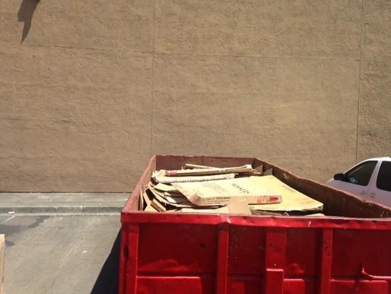 Dumpster full of cardboard behind furniture store.