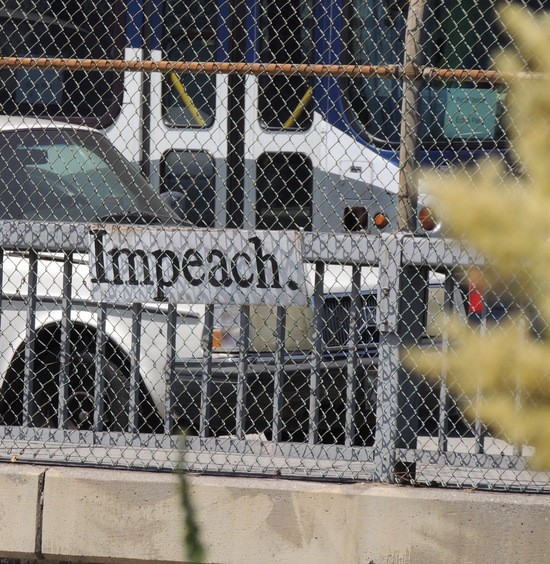 Impeach sign squeezed between fence and rail.