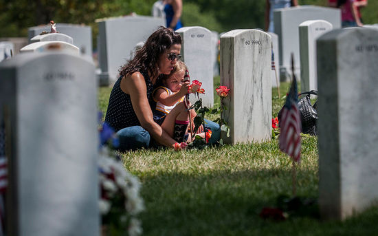 ARLINGTON, VA - MAY 25:   Angela Spraul and her daughter Ava, 4, sit at the grave of her husband John Spraul, U.S. Navy, who died Feb. 28, 2013, at Section 60 on Memorial Day at Arlington National Cemetery on May 25, 2015 in Arlington, Va. U.S. President Barack Obama, Chairman of the Joint Chiefs of Staff U.S. Army General Martin Dempsey and U.S. Defense Secretary Ash Carter honored fallen soldiers during a ceremony at Arlington on this Memorial Day.  (Photo by Gabriella Demczuk/Getty Images)