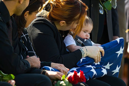 Widow Alexandra McClintock holds an American flag with her son Declan during burial of her husband US Army SGT First class Matthew McClintock at Arlington National Cemetery in Arlington, Virginia on March 7, 2016. / AFP / Jim Watson        (Photo credit should read JIM WATSON/AFP/Getty Images)