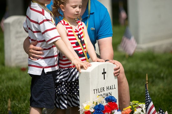 "ARLINGTON, VA - MAY 30: Eleanor Sitkiewicz, 4, of Richmond, Virginia, stands with her brother Henry, 7, and father Greg at the grave of Tyler Hall Brown, a college friend of her father, in Section 60, the burial ground for military personnel killed since 2001, at Arlington National Cemetery on May 30, 2016 in Arlington, Virginia. Brown was killed in Iraq in 2004 and Greg has been bringing his wife Sara and later the whole family to the grave site since then. ""There is nothing else we have done that consistently for so long,"" says Sara.  ""Tyler has changed the meaning of Memorial Day for us."" (Photo by Allison Shelley/Getty Images)"