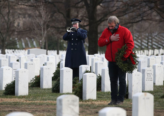 ARLINGTON, VA - DECEMBER 19: A passer-by stopped, as a US Air Force Buglar played Taps during a full honor burial service for Air Force Maj. Troy Lee Gilbert, at Arlington Cemetery, December 19, 2016 in Arlington, Virginia. Maj. Smith killed when his F-16C Fighting Falcon crashed 20 miles northwest of Baghdad, Iraq on November 27, 2006 while engaged in support of coalition ground combat operations.  (Photo by Mark Wilson/Getty Images)