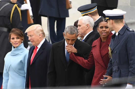 Former President Barack Obama(C)kisses the hand of Michelle Obamaas they walk with President Donald Trump and First Lady Melania Trump(L) before departing the US Capitol after inauguration ceremonies at the US Capitol in Washington, DC, on January 20, 2017. / AFP / JIM WATSON        (Photo credit should read JIM WATSON/AFP/Getty Images)