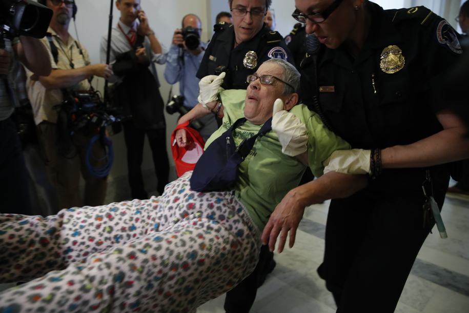 People are removed from a sit-in outside of Senate Majority Leader Mitch McConnell's office as they protest proposed cuts to Medicaid, Thursday, June 22, 2017 on Capitol Hill in Washington.   (AP Photo/Jacquelyn Martin)