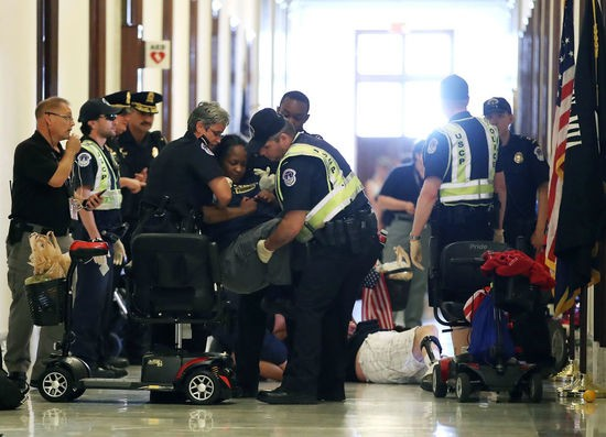U.S. Capitol Police remove protesters from in front of the office of Senate Majority Leader Mitch McConnell (R-KY) inside the Russell Senate Office Building on Capitol Hill, on June 22, 2017 in Washington, DC. Members of a group with disabilities were protesting the proposed GOP health care plan that was unveiled today.  (Photo by Mark Wilson/Getty Images)