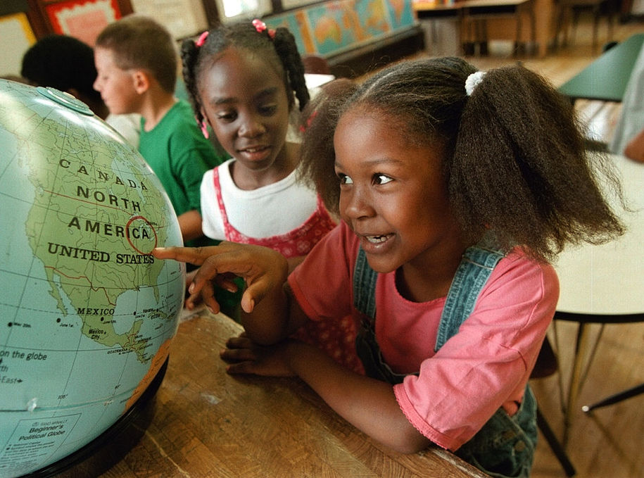 376669 02: First-grader Khatona Miller, right, investigates a circled location on a world globe with other classmates August 22, 2000 at Chicago's Stewart Elementary School. Young Khatona Miller is one of over 430,000 children heading back to the classrooms Aug. 22 in the Chicago Public School system. (Photo by Tim Boyle/Newsmakers)