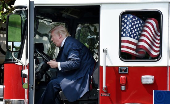 """President Donald Trump examines a fire truck from Wisconsin-based manufacturer Pierce on the South Lawn during a """"Made in America"""" product showcase event at the White House in Washington, DC, on July 17, 2017.  / AFP PHOTO / Olivier Douliery        (Photo credit should read OLIVIER DOULIERY/AFP/Getty Images)"""