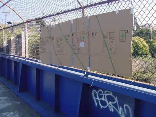 Cardboard sign attached to fencing with bungee cords and duct tape.