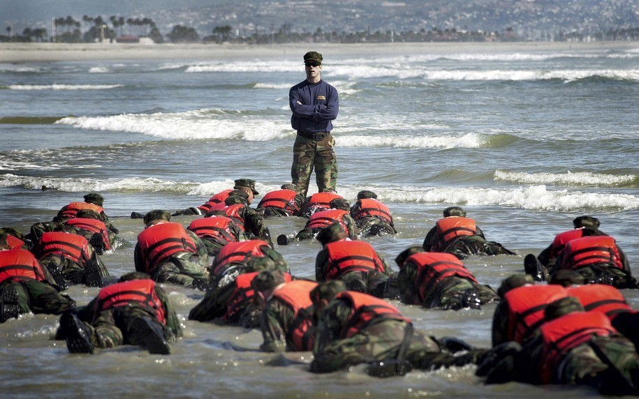 "CORONADO, CA - APRIL 15:  During a Hell Week surf drill evolution, a Navy SEAL instructor assists students from Basic Underwater Demolition/SEAL (BUD/S) class 245 with learning the importance of listening April 15, 2003 in Coronado, California. The intense physical and mental conditioning it takes to become a SEAL begins at BUD/S training. During this six-month mind and body obstacle course, recruits are pushed to their physical and mental limits. Further development of the core values, Honor, Courage, Commitment and Integrity, is an essential component of SEAL training and one that is weaved throughout a SEAL's career. First phase is the basic conditioning phase and is eight weeks in length. Physical training involves running, swimming, and calisthenics, all of which become increasingly difficult as the weeks progress. The fourth week of training, ""Hell Week,"" is five-and-a-half days of continuous training with very little sleep. This week is designed to push students to their maximum capability both physically and mentally. The remaining weeks are spent in hydrographic reconnaissance and basic maritime training.  (Photo by Photographer's Mate 2nd Class Eric S. Logsdon/U.S. Navy via Getty Images)"