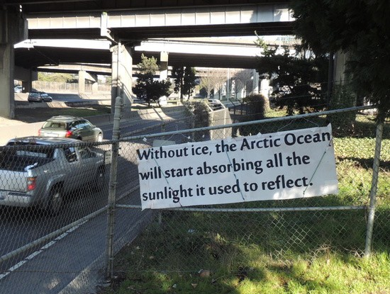 """""""Without ice the Arctic will start absorbing all the sunlight it used to reflect."""" sign next to I-5"""