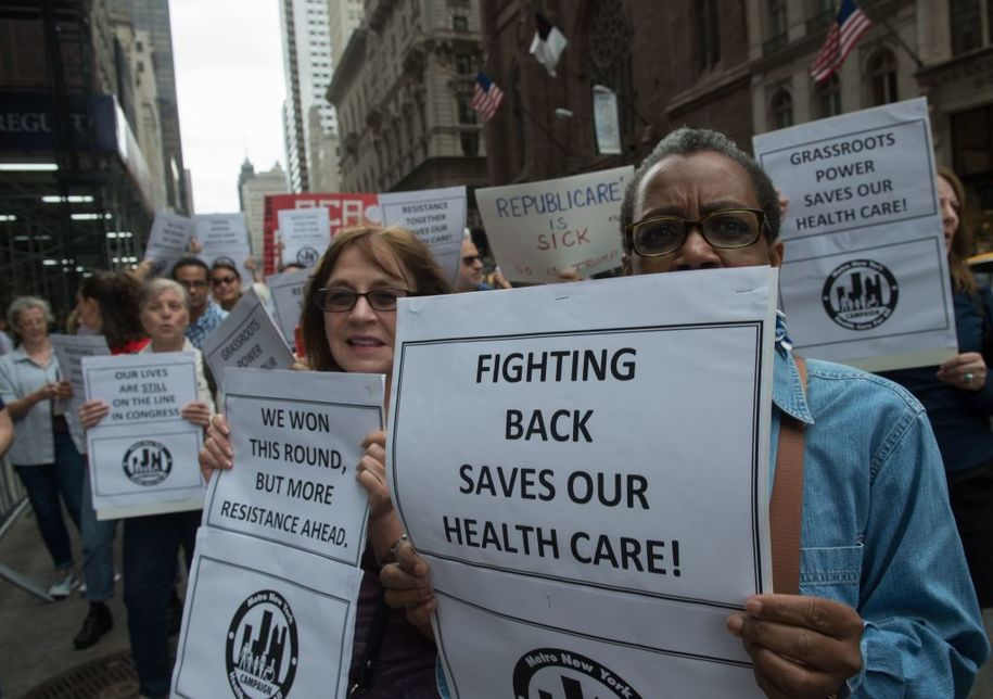 Protesters carry signs during a health care rally in front of Trump Tower on July 29, 2017 in New York.  / AFP PHOTO        (Photo credit should read /AFP/Getty Images)