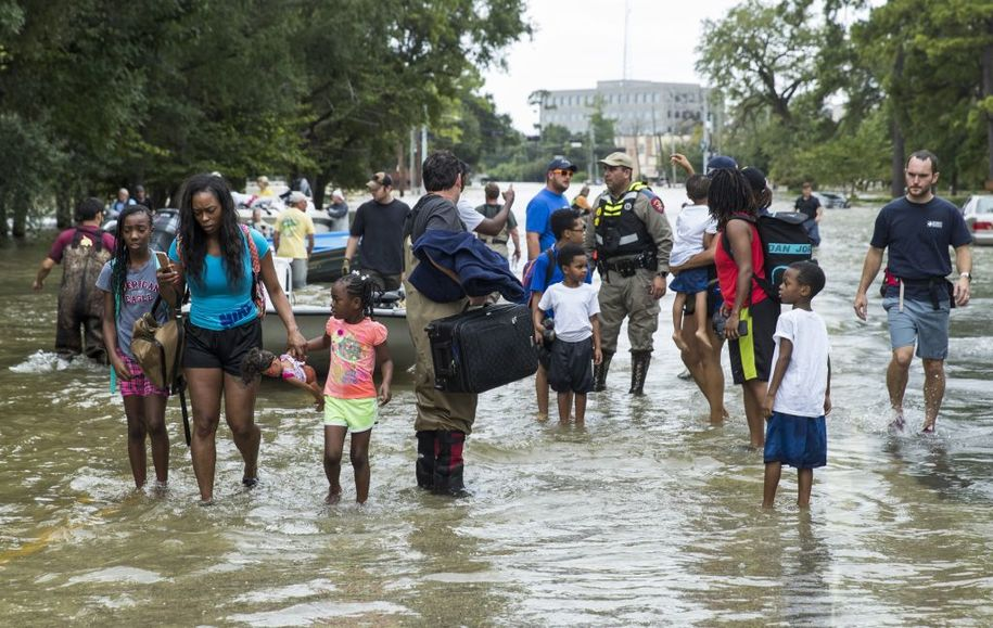 HOUSTON, TX - AUGUST 30: The Walker and Brown families walk out of the water at Memorial Drive and North Eldridge Parkway in the Energy Corridor of west Houston where residents rescued from their flooded homes and apartments due to high water coming from the Addicks Reservoir after Hurricane Harvey on August 30, 2017 in Houston, Texas. Harvey, which made landfall north of Corpus Christi August 25, has dumped more than 50 inches of rain in some areas in and around Houston. (Photo by Erich Schlegel/Getty Images)
