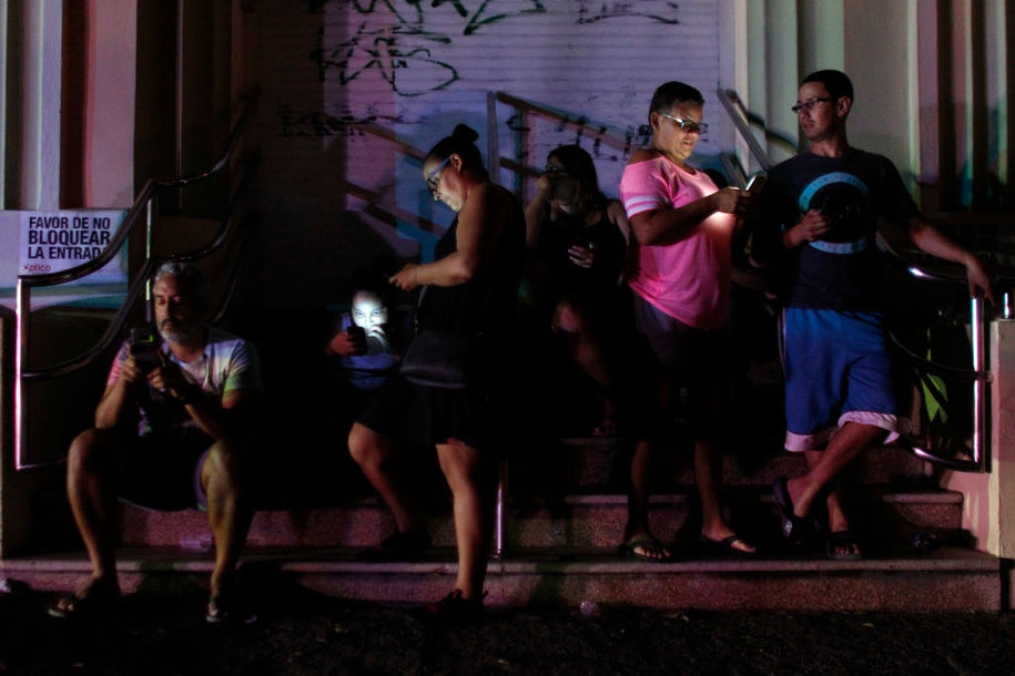 People use their cell phones at night in one of the few places with cell signal in San Juan, Puerto Rico, on September 25, 2017, where a 7pm-6am curfew has been imposed following impact of Hurricane Maria on the island.  / AFP PHOTO / Ricardo ARDUENGO        (Photo credit should read RICARDO ARDUENGO/AFP/Getty Images)