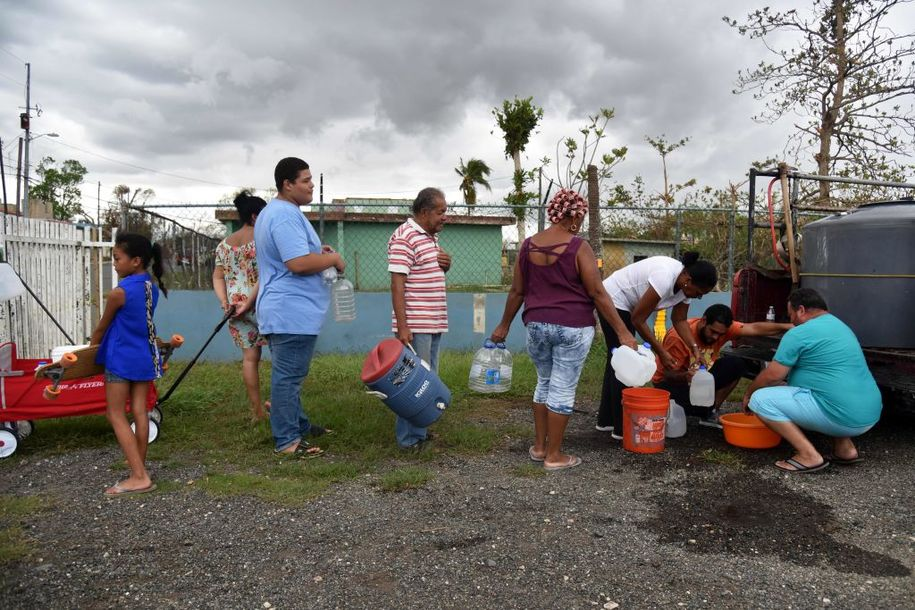 People take water from a tank in Vega Baja, Puerto Rico, on September 30, 2017, due to the lack of water after the passage of Hurricane Maria..US military and emergency relief teams ramped up their aid efforts for Puerto Rico amid growing criticism of the response to the hurricanes which ripped through the Caribbean island. / AFP PHOTO / HECTOR RETAMAL        (Photo credit should read HECTOR RETAMAL/AFP/Getty Images)