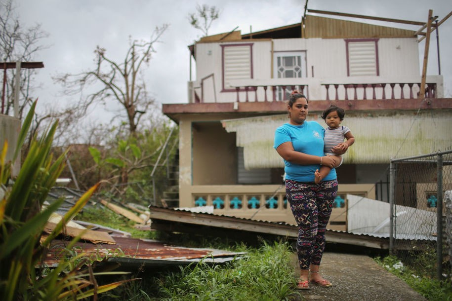 AIBONITO, PUERTO RICO - OCTOBER 11:  Yamiles Vazquez poses with her baby Joy on a section of her family's damaged property three weeks after Hurricane Maria hit the island, on October 11, 2017 in Aibonito, Puerto Rico. The area is without running water or grid power as a nightly curfew remains in effect. Despite multiple visits from FEMA, the town has yet to receive any FEMA aid. Only 10.6 percent of Puerto Rico's grid electricity has been restored. Puerto Rico experienced widespread damage including most of the electrical, gas and water grid as well as agriculture after Hurricane Maria, a category 4 hurricane, swept through.  (Photo by Mario Tama/Getty Images)